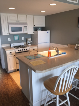 Full kitchen with stove, oven, fridge, microwave, coffee pot.