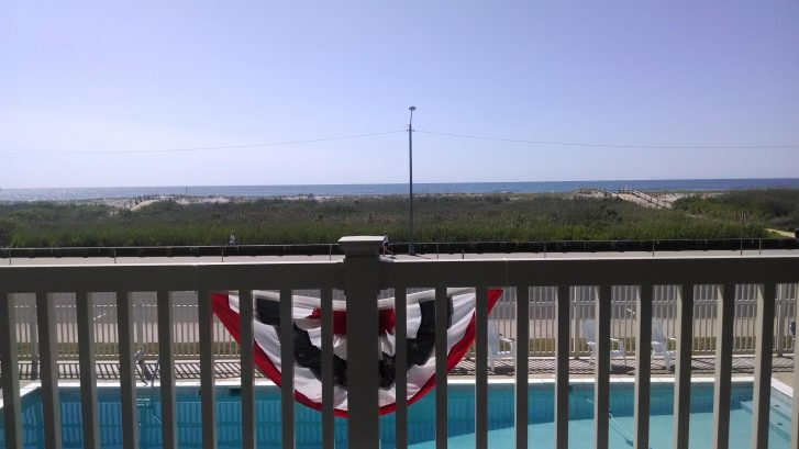 view of pool and beach from balcony