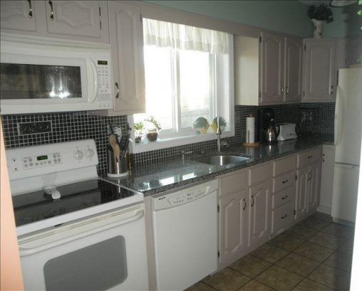 Newly remodeled kitchen with granite counter tops and tiled back splash.