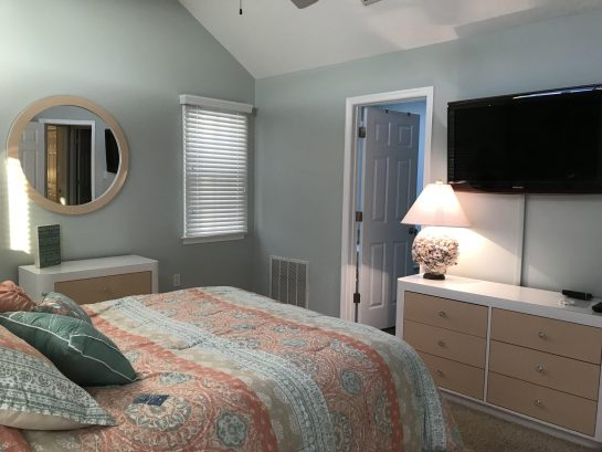 Master bedroom with queen bed, Samsung wall-mounted TV and private  master bathroom.