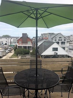 View of deck with 4 person table/chairs, umbrella & grill