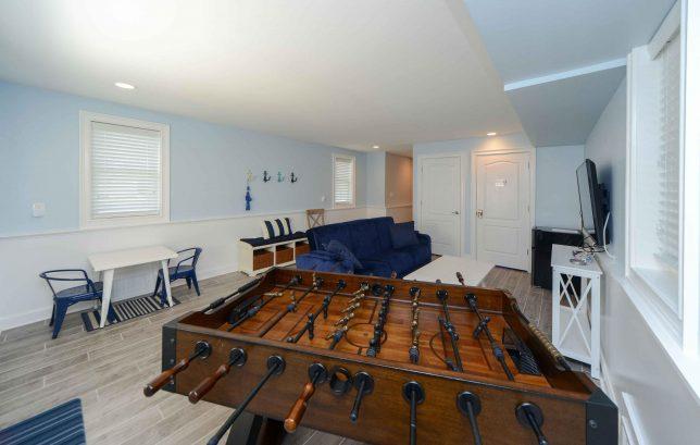 Ground level entryway recreation room with futon sofa, TV, foosball table, stairwell, elevator, garage