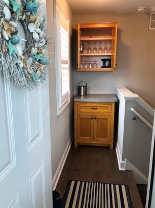 Top of stairwell mini bar with additional accessories, first aid kit, large pots, drinkware