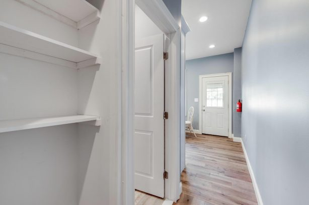 left unit hallway leading from living room past the bedrooms + bathroom into kitchen