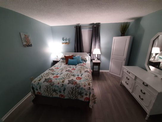 Spacious one bedroom has queen bed, storage cabinet,  & dresser.